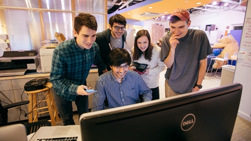 a group of students gathered around a computer