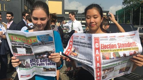 two female students reading newspapers