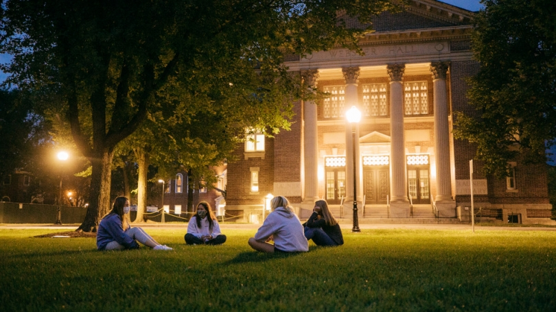 Students sit on the green at night