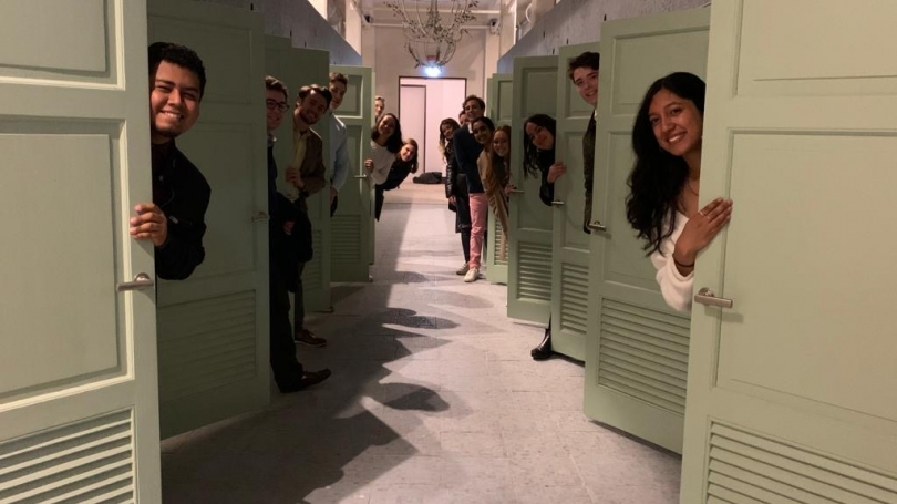 Students posing behind doors in Rome, Italy