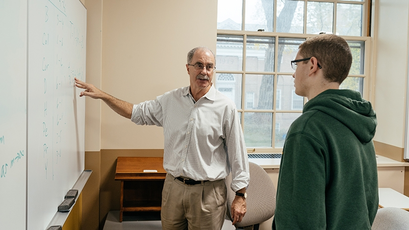 Phil Hanlon '77 standing with a student at a white board